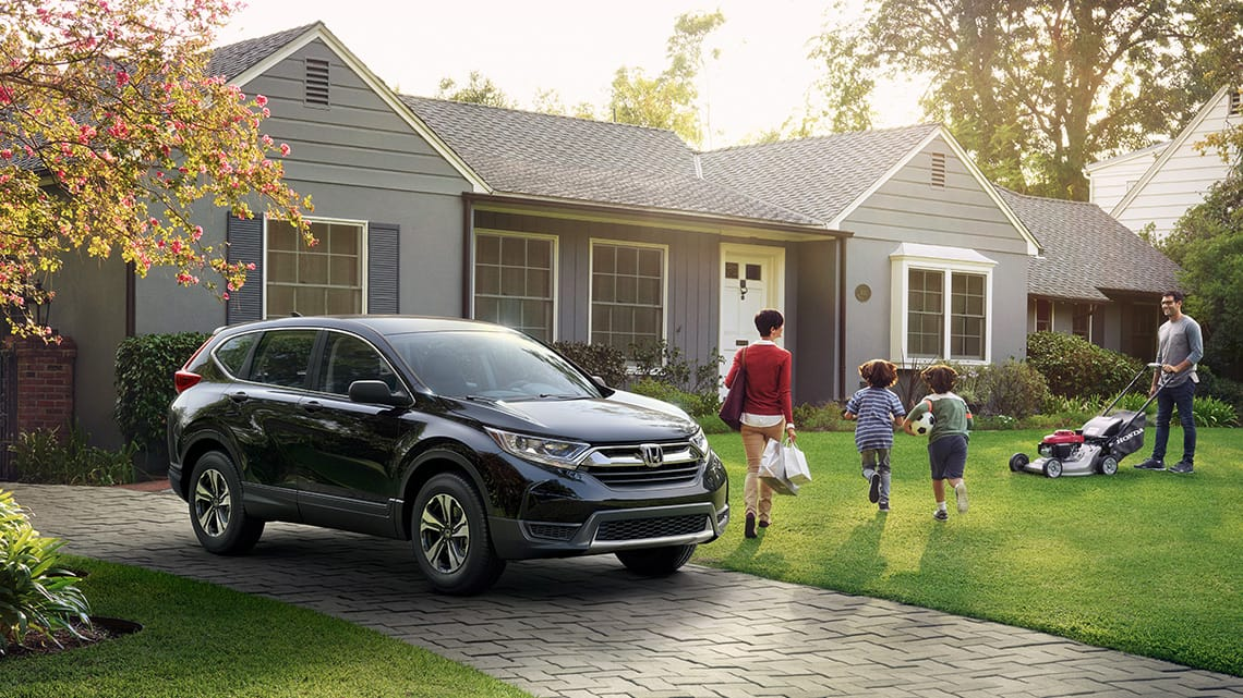 Side profile view of 2019 Honda CR-V Touring in Dark Olive Metallic with Honda Genuine Accessory short roof box and crossbars.