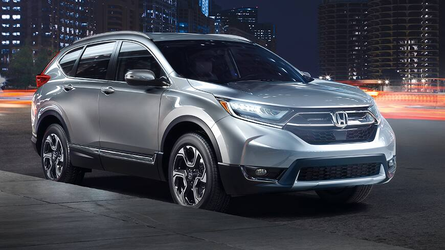Front 3/4 view of 2019 Honda CR-V Touring in Lunar Silver Metallic showing full LED headlights with auto-on/off.