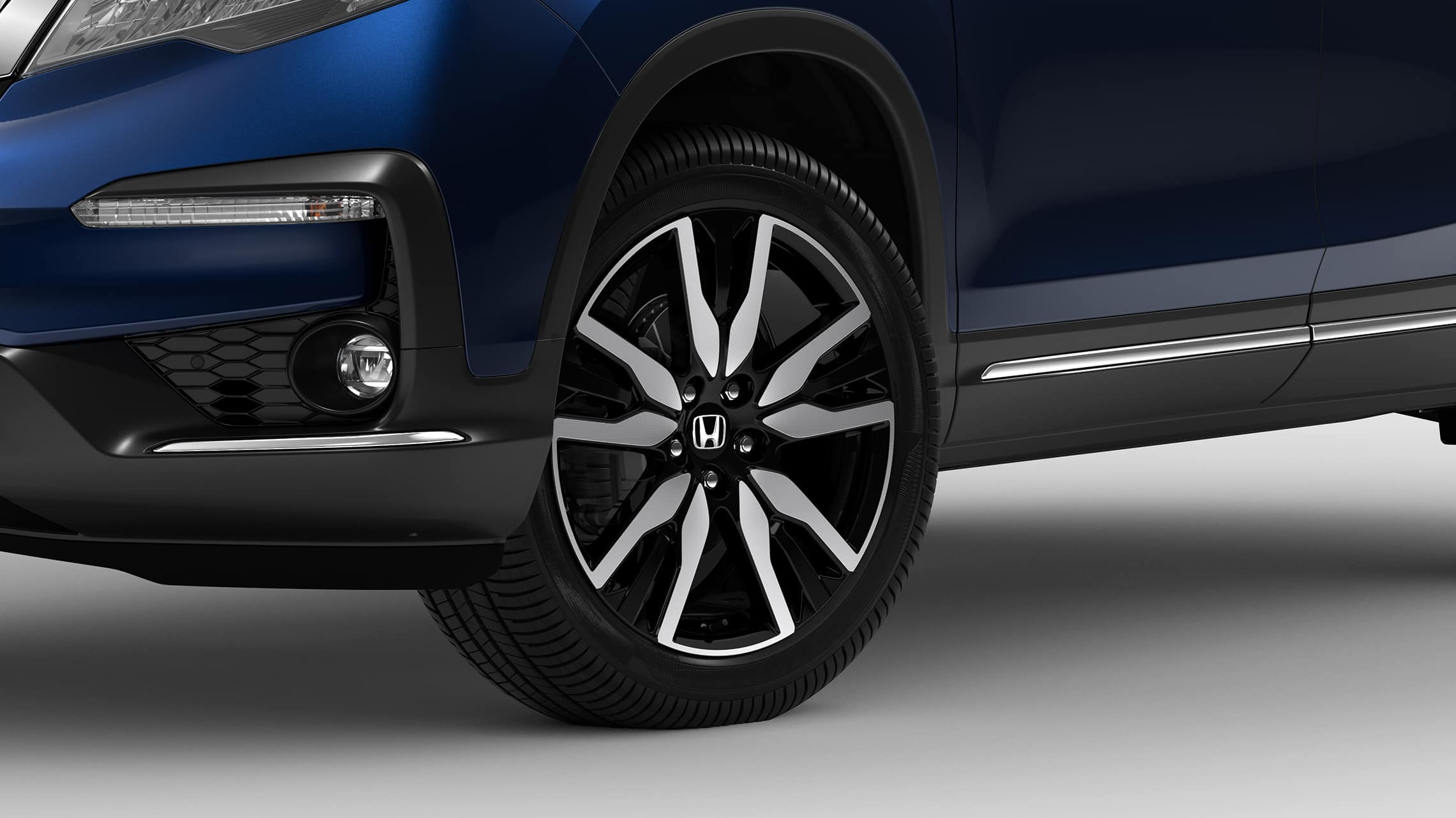 Front 3/4 driver's side close-up view of 20-Inch Alloy wheel and tire detail on 2020 Honda Pilot Elite in Steel Sapphire Metallic.